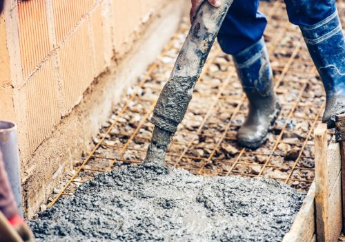 close-up-of-industrial-worker-pouring-cement-or-PSKNQML